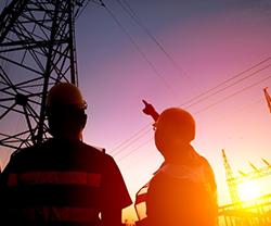 Imagen de dos trabajadores mirando una torre de alta tensión