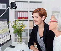 Imagen de dos mujeres, una mayor y otra joven mirando la pantalla de un ordenador