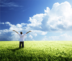 Imagen de un hombre con los brazos en alto respirando profundo en el campo