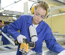 Imagen de una joven trabajadora en una fábrica, cortando una pieza con una sierra circular