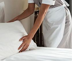 Camarera de piso colocando el almohadón de una cama en un hotel