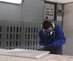 Imagen de un trabajador con equipo de protección en rostro, cortando una pieza de marmol