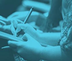 Imagen de unas manos de mujer escribiendo sobre un cuaderno
