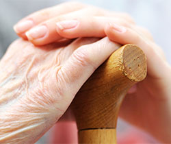 Imagen de unas manos de mujer mayor apoyadas sobre un bastón