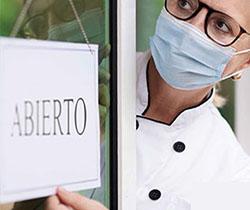 Imagen de una hostelera con mascarilla abriendo la puerta de su local con el cartel de abierto